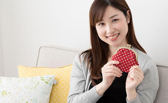 お財布を持つ笑顔の女性